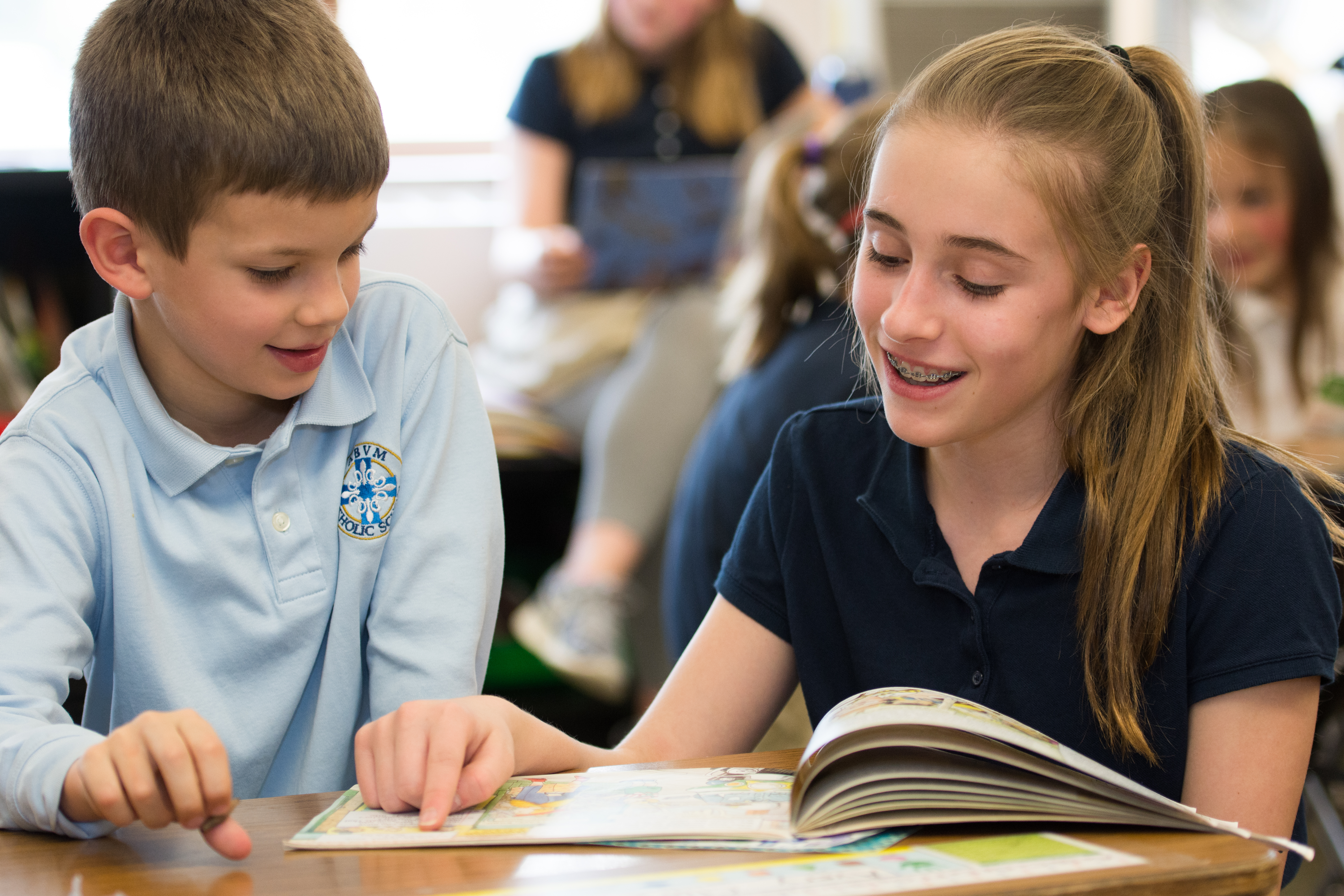 two school-age children, a boy and girl, read together at assumption of the blessed virgin mary catholic school in belmont, michigan