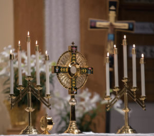 a monstrance is flanked by two sets of candles on an altar