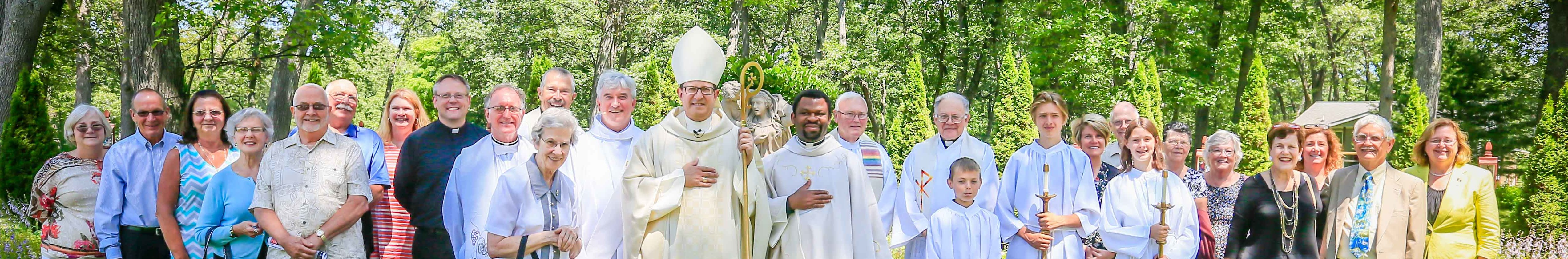 bishop walkowiak poses with fr. godfrey onyekwere and parishioners of st. mary of the woods in muskegon