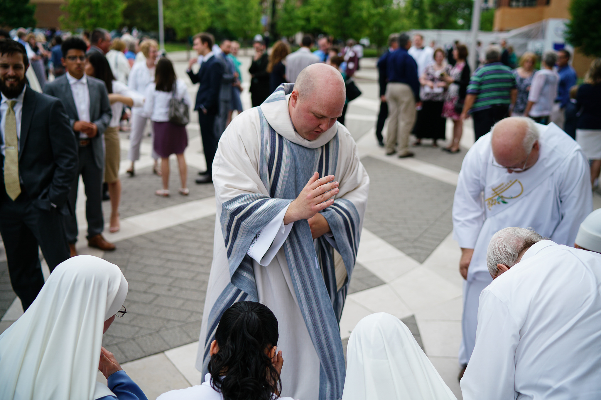 father stephen durkee gives a blessing to the crowd following his ordination to the priesthood