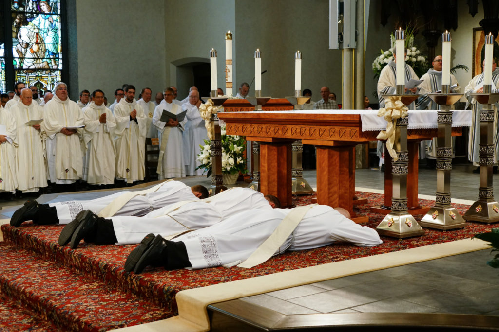 three candidates lay prostrate in front of the altar before their ordination to the priesthood
