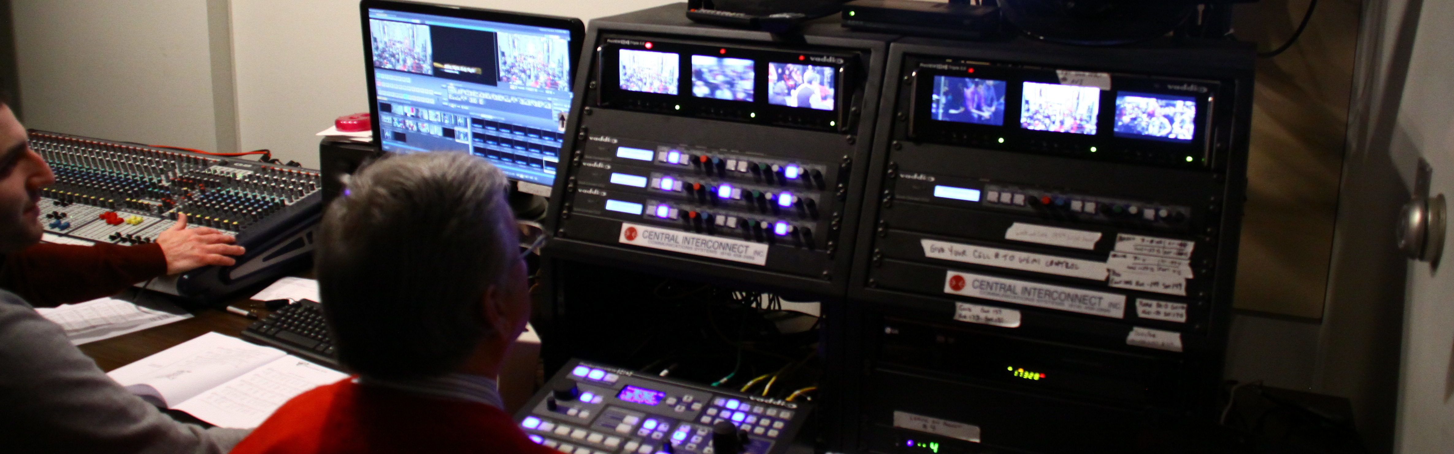 two men sit in the control room at the cathedral of saint andrew for a live broadcast of mass