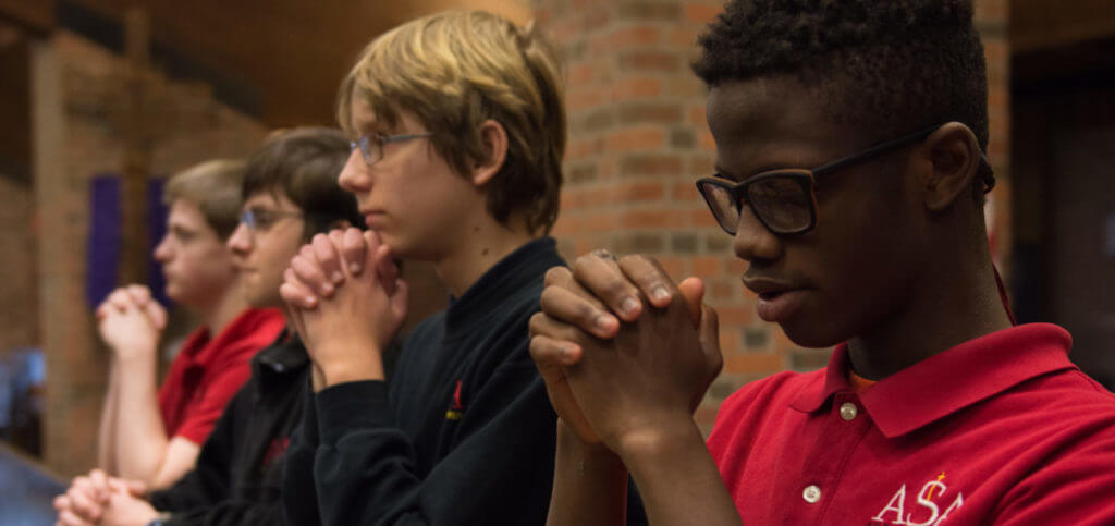 four middle school boys praying in a pew at st. jude catholic church in grand rapids, michigan