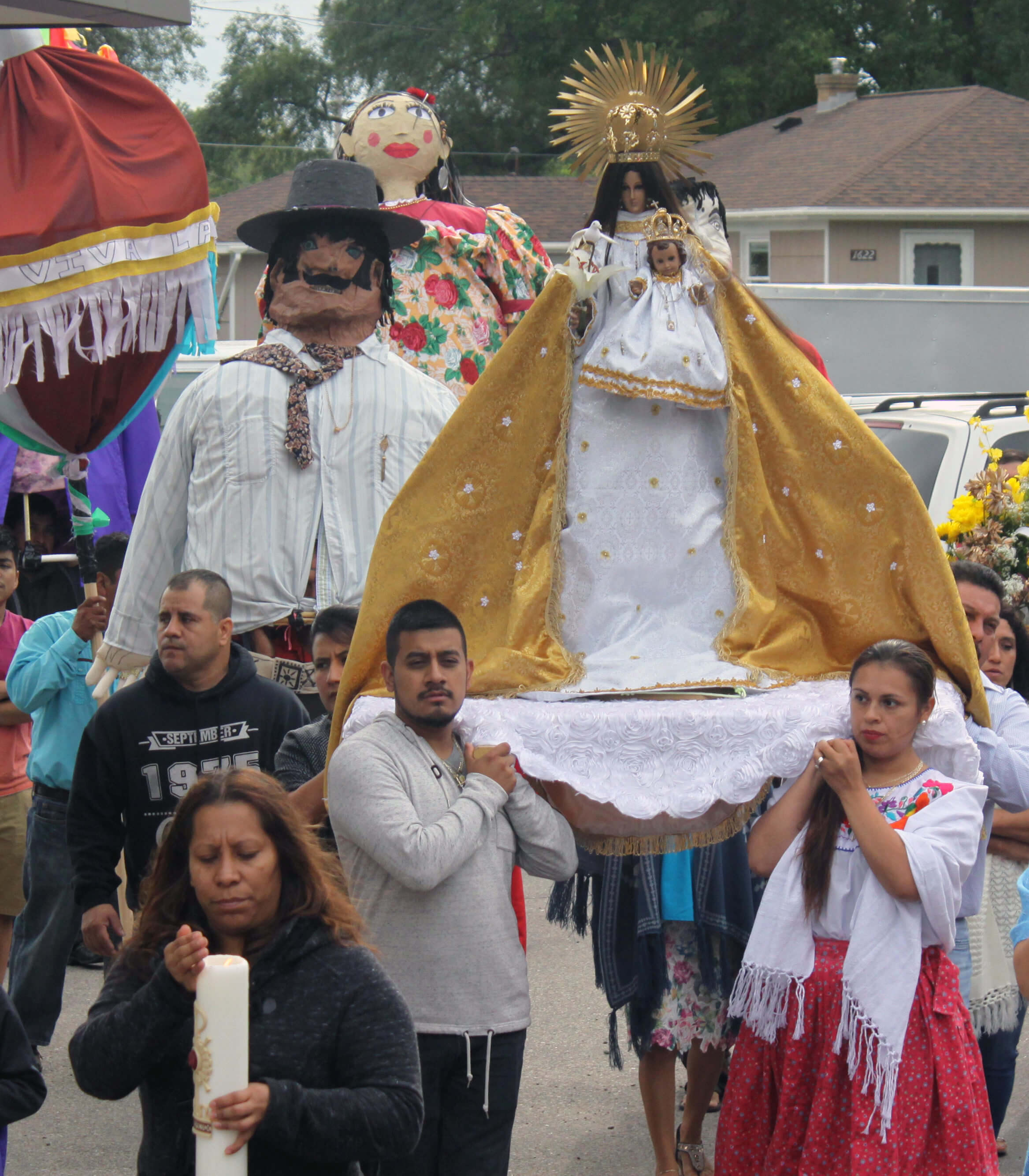 a crowd of hispanic catholics carry a statue of the virgin mary in a procession to mark the nativity of her birth outside holy name of jesus parish in wyoming, michigan