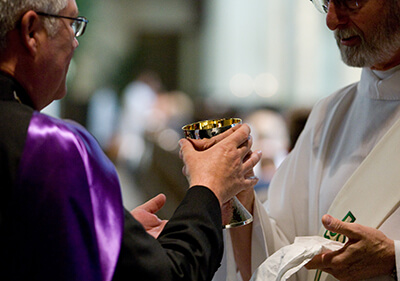 Deacon offers the chalice to a Mass attendee during holy Communion