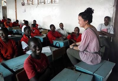 Maryknoll lay missioner teaches a classroom of young people