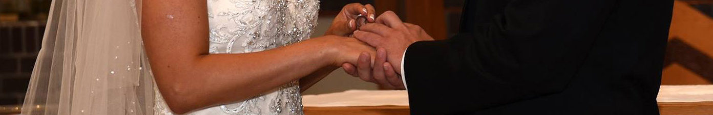 close up of a couple's hands while exchanging rings during a wedding mass at holy spirit parish in grand rapids, michigan