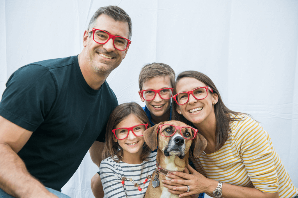 carl and kelly jandernoa pose with their children with red glasses on to promote the red glasses movement