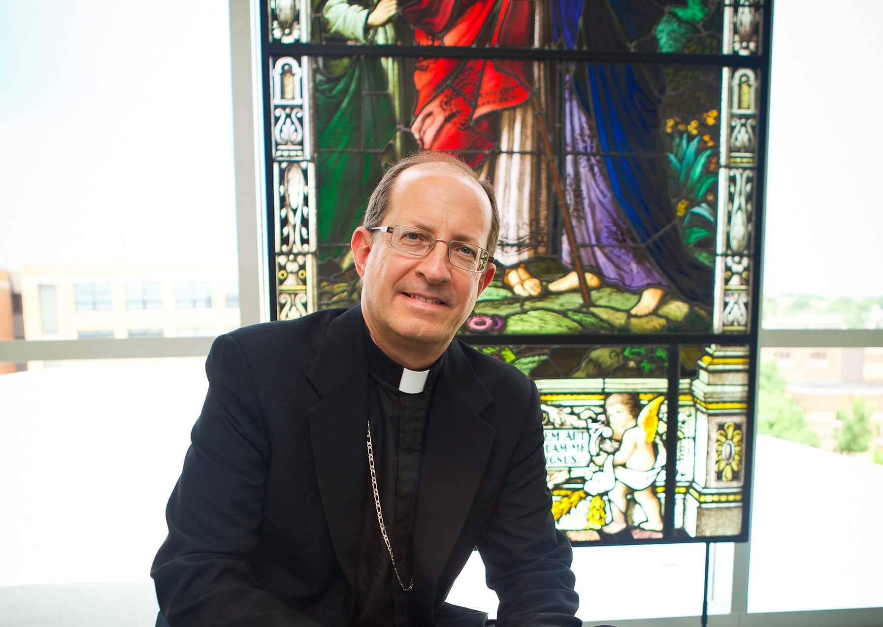 Bishop Walkowiak sits near a stained glass window at Cathedral Square Center