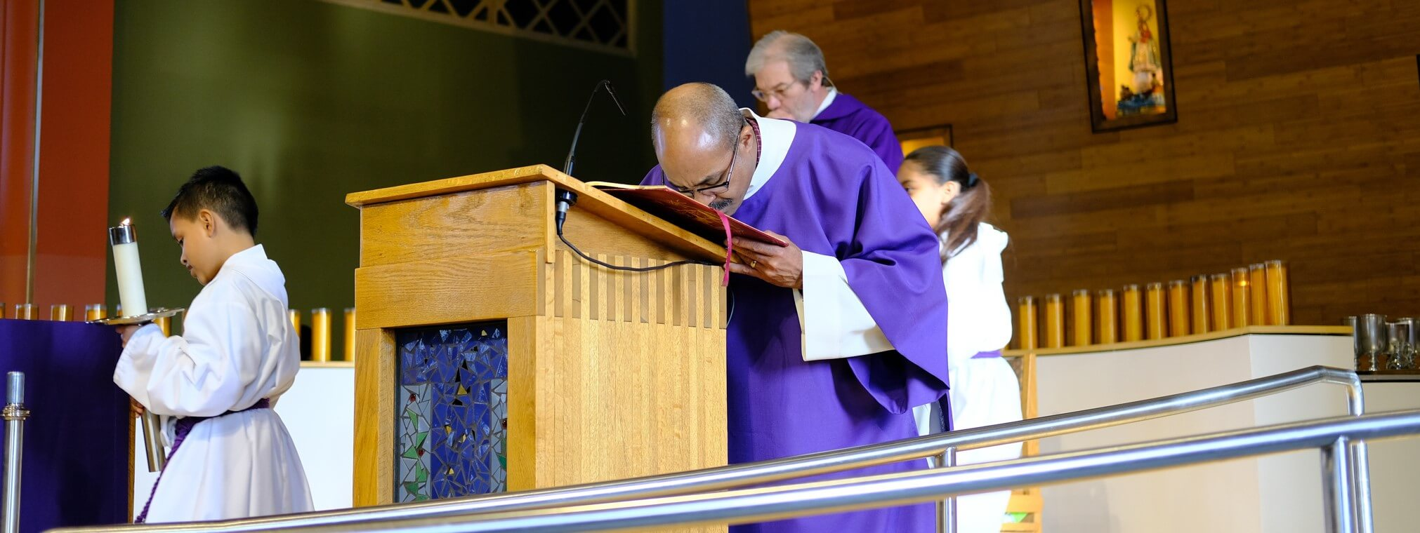 Deacon Carlos Guiterrez kisses the Book of Gospels after the Sunday reading at Saint Joseph the Worker parish