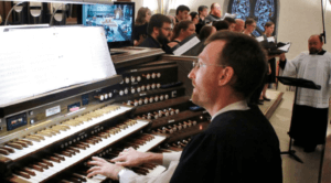 Image from the choir loft of the Cathedral of Saint Andrew of organist, choir members and music director