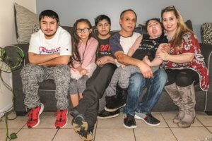 The Eduardo family poses for a photo on their couch