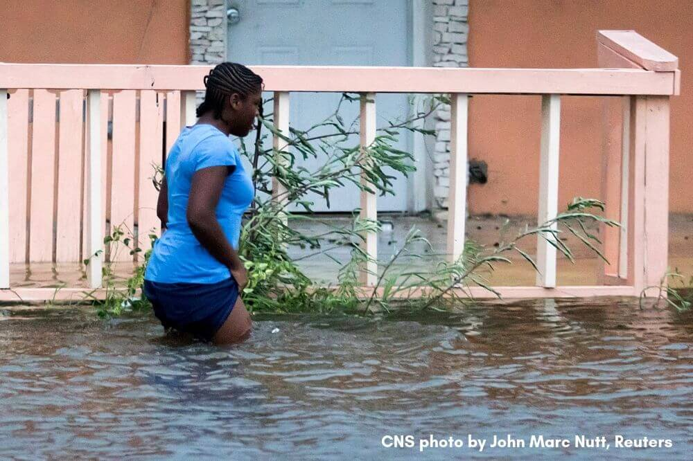 CNS photo shows woman wading through floodwater following Hurricane Dorian, September 2019 by John Marc Nutt, Reuters