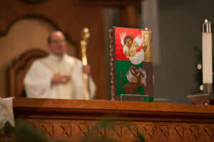 Image of the book of gospels with Bishop Walkowiak in background, Christmas midnight Mass 2016 by Eric Tank