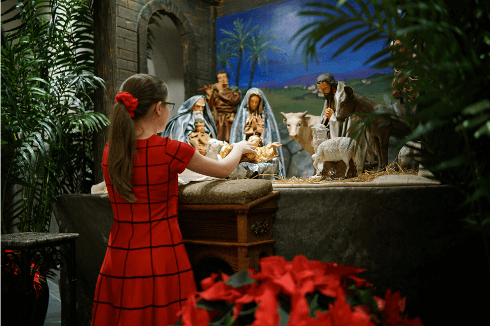 Child places baby Jesus in manger during Christmas midnight Mass at Cathedral of Saint Andrew