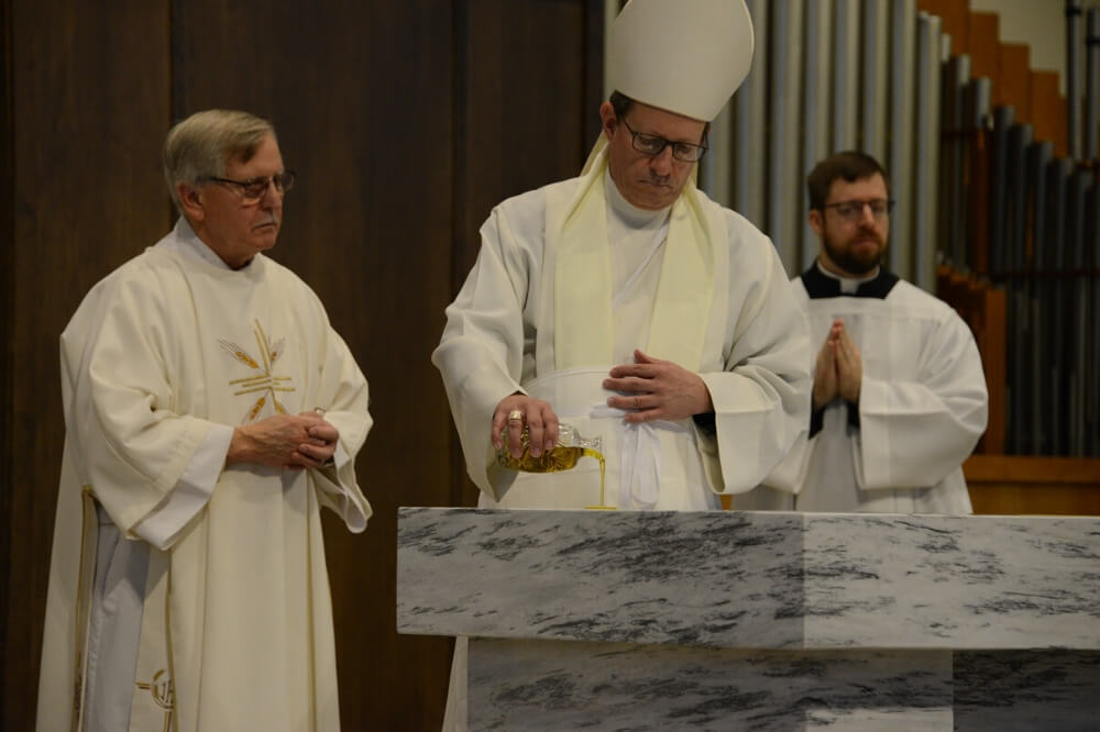 Bishop Walkowiak pours holy oil onto the altar during dedication Mass for St. John Paul II Church, Cedar Springs