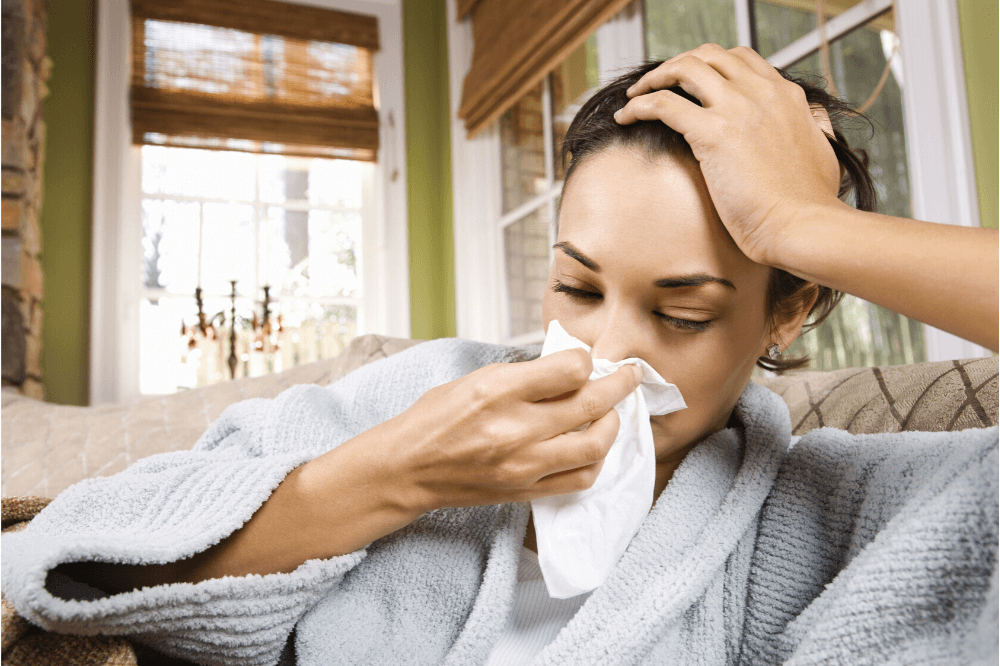 Image of young woman in robe with tissue, cold and flu season