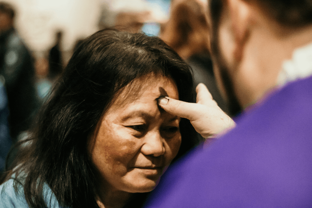 Ash Wednesday Mass 2020 photo, woman receiving ashes by Emma Rolf